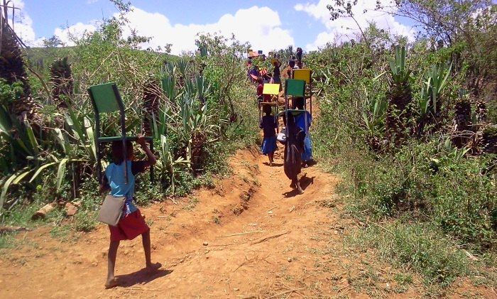 Children at Lemolo happily carry their new chairs to their school